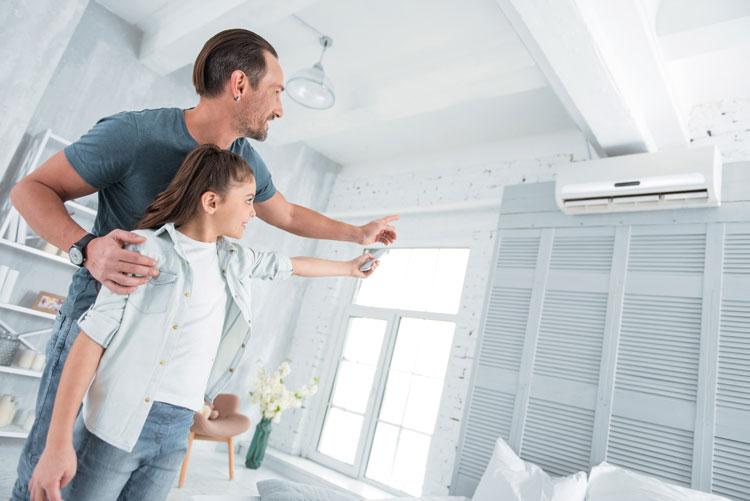 Vater und Tochter steuern mit Fernbedienung Smart Home-Klimaanlage